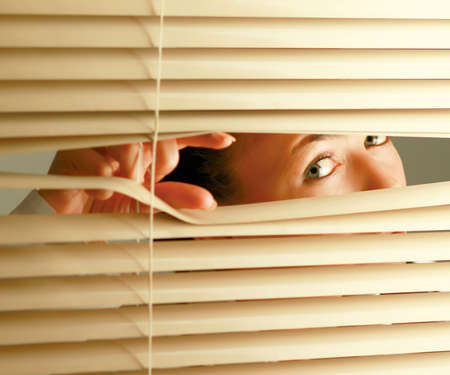 jalousie: Portrait of a woman looking through out the blinds. Stock Photo
