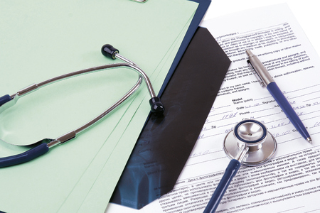 Stethoscope on medical billing statement on table, all text is anonymous.
