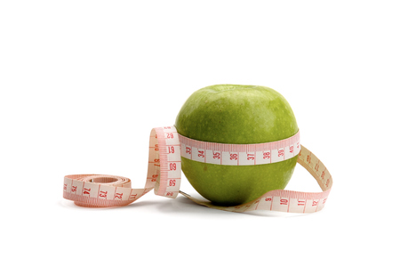unattached: A green apple and a measuring tape, isolated on white background.