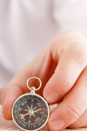 orienting: Man's hand holding a compass.