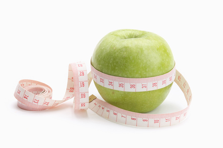 unattached: A green apple and a measuring tape isolated on white background Stock Photo