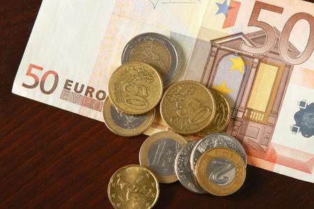 dinero euros: Dinero: monedas y billetes de euro se cierran para arriba aislado en el fondo de madera