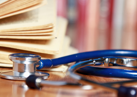 scientific literature: A stethoscope is lying with a book on the desk against books