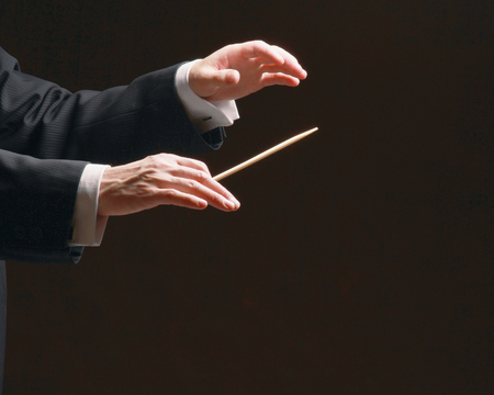 Concert conductor's hands with a baton, isolated on a black background