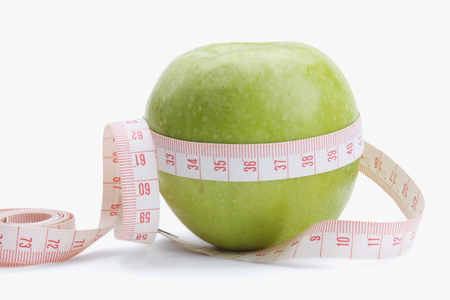 unattached: A green apple and a measurement tape , isolated on white background.