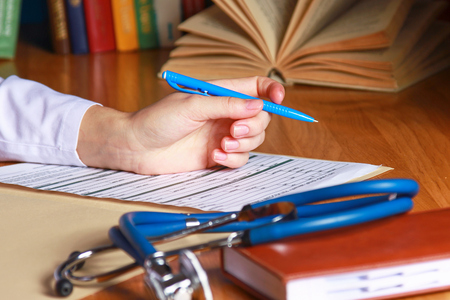 scientific literature: Close-up of writing doctor's hands on a wooden desk. Stock Photo