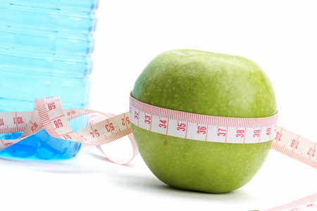 unattached: A green apple, a bottle of water and a measuring tape