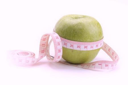 unattached: A green apple and a measurement tape, isolated on white
