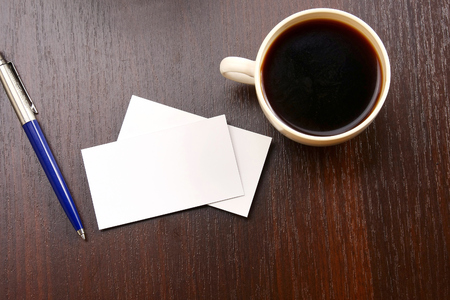 A cup of coffee, empty cards and a pen on a wooden table, from above photo
