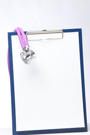 A medical stethoscope on a clipboard, isolated on white photo