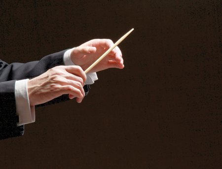 louder: Concert conductor hands with a baton isolated on a black background