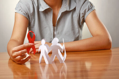 Female hands holding paper people and a red hiv ribbon, closeup Stock Photo