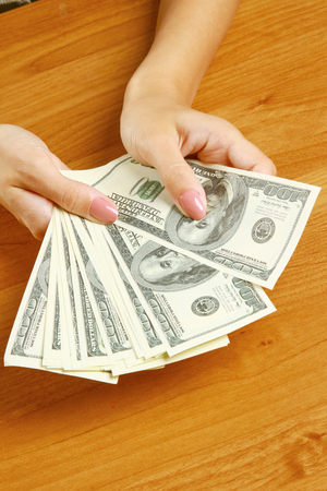 greediness: Female hands holding dollars, closeup Stock Photo