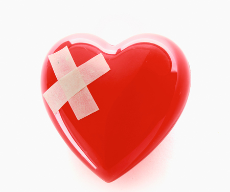 mended: A red heart with adhesive plaster isolated on white background