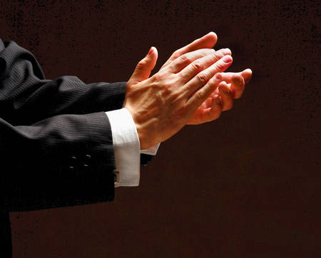 sideview: Male hands clapping on black, side-view Stock Photo