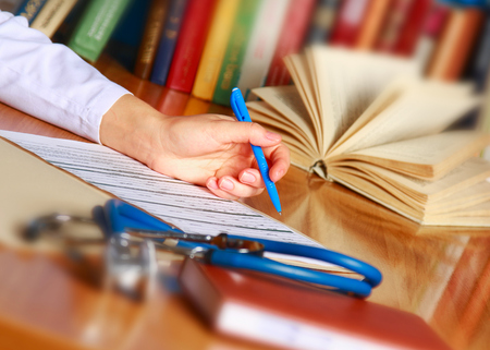 scientific literature: Close-up of writing doctor's hands on a wooden desk Stock Photo