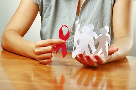 A woman holding paper peolple and an aids red ribbon photo