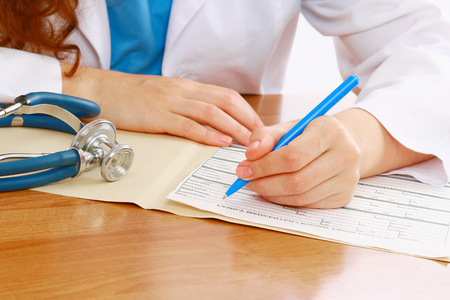 A female doctor is fiiling a prescription - close-up photo