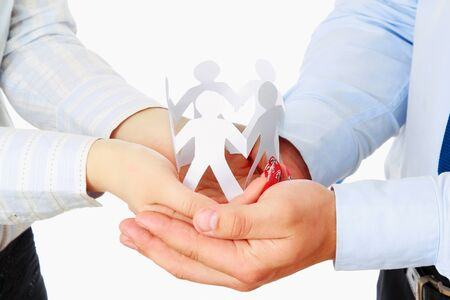 cooperating: Business couple with paper people isolated. Focus on hands Stock Photo