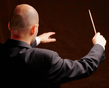backview: Concert conductor with baton isolated on  black background, back-view Stock Photo