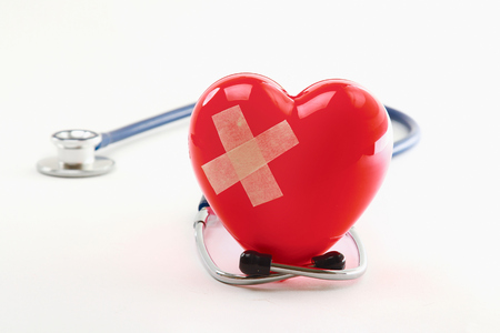 Broken heart with a stethoscope, isolated on white background photo