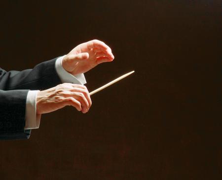 コンサートの指揮者 ' で黒の背景に分離されたバトンの手