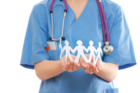 A female doctor holding paper people, focus on the hands photo