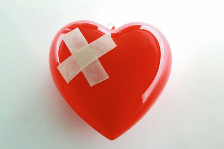 mended: Red heart with adhesive plaster isolated on white background