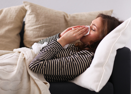 poorly: Portrait of a sick woman blowing her nose while sitting on the sofa Stock Photo