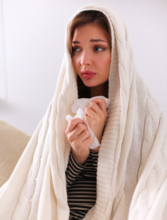 grippe: Sick woman covered with blanket holding cup of tea sitting on sofa couch Stock Photo