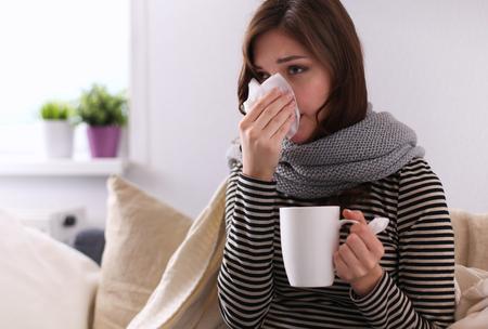 chory: Chora kobieta pokryte koc gospodarstwo filiżanka herbaty siedzi na kanapie sofie Zdjęcie Seryjne