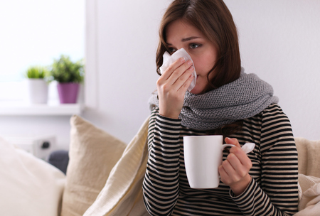 Sick woman covered with blanket holding cup of tea sitting on sofa couch Foto de archivo