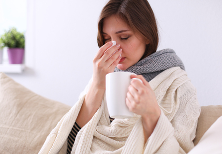 flu virus: Portrait of a sick woman blowing her nose while sitting on the sofa Stock Photo