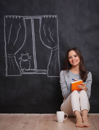 untroubled: Young woman sitting on the floor near dark wall with painted a window Stock Photo