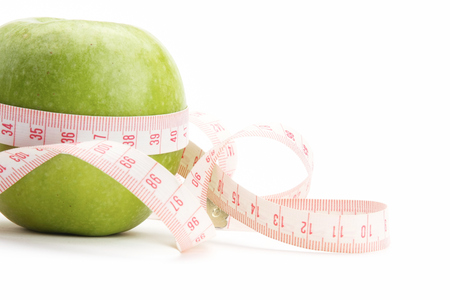 unattached: A green apple and a measurement tape Stock Photo