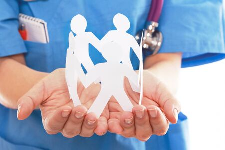 A female doctor holding paper people, focus on the hand photo