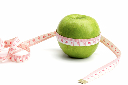 unattached: A green apple and a measuring tape Stock Photo