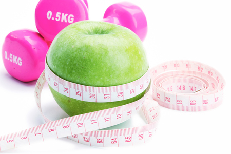 unattached: An apple, a measuring tape and dunbbell