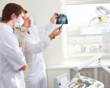 Dentist holding an x-ray and standing near chair photo