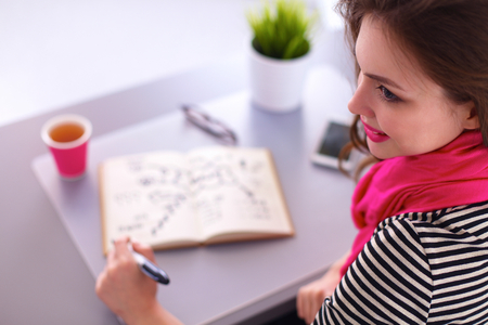 diary: Young woman writes to diary on a white table Stock Photo