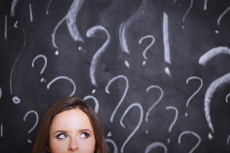 灰色の背景に疑問符を持つ少女