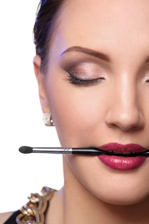 make up brush: Womans lips holding make up brush