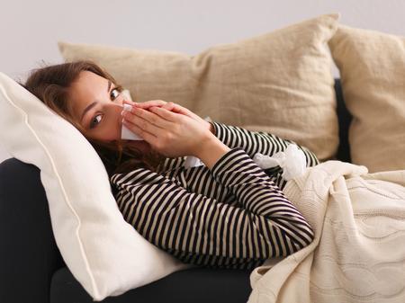 chory: Portret chorej dmuchanie jej nosa, siedząc na kanapie Zdjęcie Seryjne