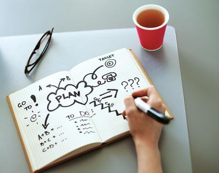若い女性が白いテーブルの日記に書き込みます