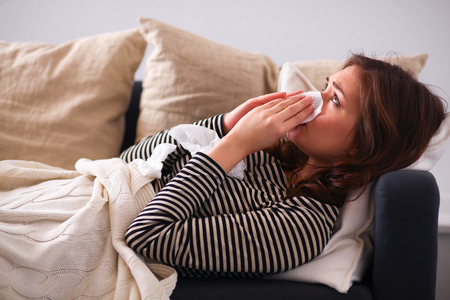 woman blowing: Portrait of a sick woman blowing her nose while sitting on the sofa Stock Photo