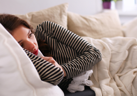 feeble: Portrait of a sick woman blowing her nose while sitting on the sofa Stock Photo
