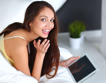 plane table: Women use a tablet pc on the bed Stock Photo