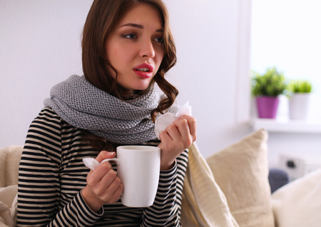 Sick woman covered with blanket holding cup of tea sitting on sofa couch Zdjęcie Seryjne
