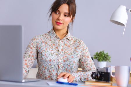 female photographer: Female photographer sitting on the desk with laptop Stock Photo