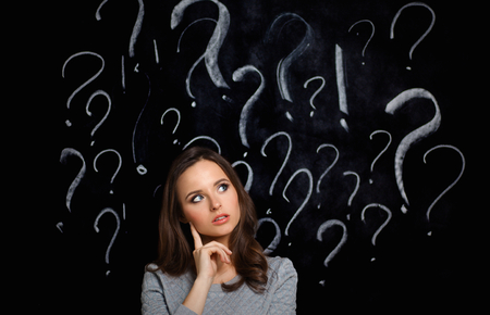Jong meisje met een vraagteken op een grijze achtergrond Stockfoto
